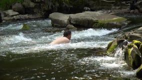Facet pływa w rzece Młody śliczny facet kąpać w czystej halnej rzece Jest szczęśliwy zbiory