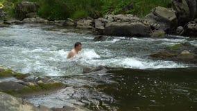 Facet pływa w rzece Młody śliczny facet kąpać w czystej halnej rzece Jest szczęśliwy zdjęcie wideo