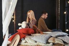Facet patrzeje w różnych kierunkach z dziewczyny obsiadaniem na zamyśleniu i łóżku obrazy stock