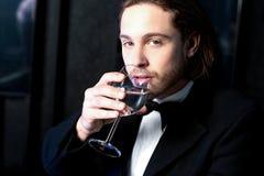 Facet pije koktajl w smokingu Fotografia Stock