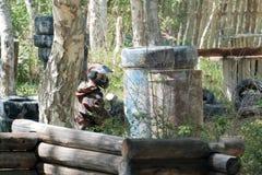 Facet podczas gry paintball na wysypisku Kamuflażu kostium, ochronna maska i bronie, Opony, baryłki, drewniani ogrodzenia w t zdjęcie royalty free