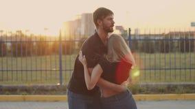 Facet podnosi w górę jego dziewczyny i kłębi z ona swobodny ruch Para w miłości przy zmierzchem zbiory