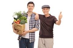 Facet pomaga starszego mężczyzna z sklepami spożywczymi Zdjęcia Stock