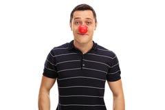 Facet pozuje z czerwonym błazenu nosem Zdjęcia Royalty Free