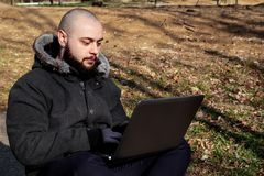 Facet pracuje na laptopie w parku Obrazy Stock