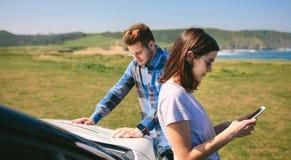 Facet przyglądająca mapa podczas gdy jego dziewczyn spojrzenia przy wiszącą ozdobą zdjęcia royalty free