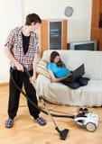 Facet robi domowemu cleaning podczas dziewczyny odpoczywać Zdjęcia Royalty Free