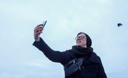 Facet robi selfie na smartphone, bpack i bielu plenerowych, Zdjęcie Stock