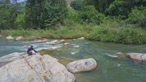 Facet Siedzi na kamieniu z torbami Innych nury w rzekę wśród gwałtownych zbiory
