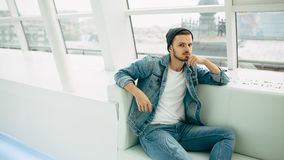 Facet siedzi na kanapie i główkowaniu Obraz Stock