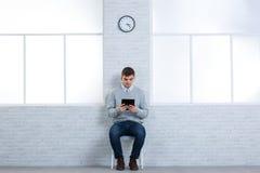 Facet siedzi na krześle blisko ściany z zegarem i używa pastylkę fotografia royalty free