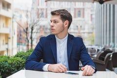 Facet siedzi przy stołem w kawiarni Na stole jest smartphone Na lewa ręka zegarku zdjęcie stock