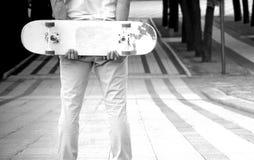 Facet stoi w parku z deskorolka w jego rękach zdjęcia stock