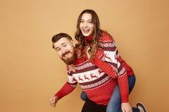 Facet trzyma dalej jego plecy dziewczyna i ubiera w czerwonych i białych pulowerach z rogaczami w studiu na beżowym tle obraz royalty free