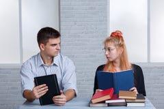 Facet trzyma ebook i dziewczyny chwyty ordynariusz książka młodzi ludzie patrzeją each inny z dobroczynnością obrazy stock