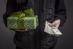 Facet trzyma pudełko z prezentem w jeden pieniądze w i ręce obrazy stock