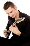 Facet ubierający w czerni ubraniach siedzi gitarę i bawić się Zdjęcie Royalty Free