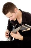 Facet ubierający w czerni ubraniach siedzi gitarę i bawić się Obraz Royalty Free