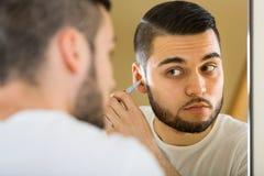 Facet usuwa włosy od jego ucho obraz royalty free