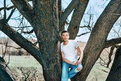 Facet w białej koszulce i niebieskich dżinsach siedzi między drzewami obraz royalty free