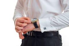 Facet w białych koszula spojrzeniach przy jego zegarkiem na jego ręce odizolowywającej na białym tle Zdjęcia Stock