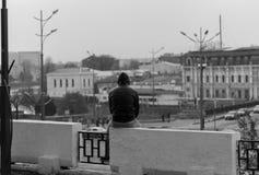 Facet w czarnej kurtce siedzi nad urwiskiem zdjęcia stock