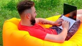 Facet w czerwonej koszulce kłama na lotniczym działaniu na laptopie i leżance Biznesmen z brodą - freelancer lub gamer w na zbiory