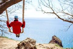 Facet w czerwonej kurtce jedzie na chela przegapia morze i kołysa fotografia stock