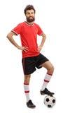 Facet w czerwonym dżersejowym odciskaniu futbol z jego stopą obrazy stock