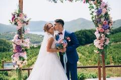 Facet w eleganckim kostiumu delikatnie całuje jego dziewczyny, i ono uśmiecha się szeroko Dzień ślubu, kochankowie pozuje przeciw obraz royalty free