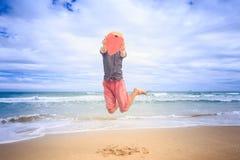 Facet w kapeluszy chwytów Ręcznie robiony Czerwonym sercu Skacze Wysoko up na plaży Zdjęcie Stock
