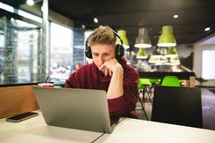 Facet w przypadkowej odzieży i hełmofonach siedzi przy stołem w kawiarni, pracuje na laptopie, skupiającym się na ekranie obraz stock