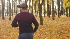 Facet w rzeczywistości wirtualnej słuchawki biega w jesień parku, mężczyzna w wspinającym się pokazie Zapalony gamer Liścia spade zbiory