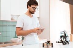 Facet w szkło stojakach w chwytach i kuchni smartphone w jego wręcza Kontroluje robot z smartphone Obrazy Stock