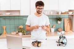 Facet w szkło stojakach w chwytach i kuchni smartphone w jego wręcza Kontroluje robot z smartphone Obraz Stock