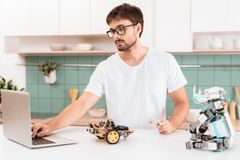 Facet w szkło stojakach w kuchni i angażuje w programować robot W pobliżu jest laptop Zdjęcie Stock