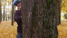 Facet w wspinającym się pokazie krzyczy i chuje za drzewem, mężczyzna w rzeczywistości wirtualnej słuchawki jest w jesień parku d zbiory