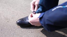 Facet wiąże jego shoelaces i wiąże koronki na butach zamknięty upThe facet zatrzymuje Buty zamykają up zdjęcie wideo