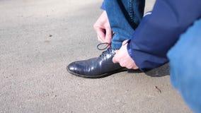 Facet wiąże jego shoelaces zamknięty up Facet zatrzymuje koronki na butach i wiąże Buty zamykają up zdjęcie wideo