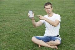 Facet wskazuje palec przy telefonem Obraz Royalty Free