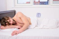 Facet wyczerpująca męcząca potrzeba więcej czas odświeżać Mężczyzna nieogolony nieatutowy łóżko z budzikiem Kija sen rozkład ten  obrazy stock