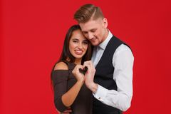 Facet z dziewczyną łączył ręki w postaci serca na czerwonym tle Zdjęcie Stock