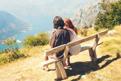 Facet z dziewczyną siedzi na ławce w Kotor zatoce Szczęśliwy rodzina składająca się z czterech osób chodzi w górach zarygluj skła obraz royalty free