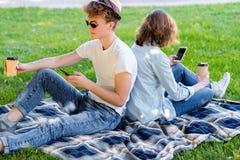 Facet z dziewczyną siedzi na koc Lato w naturze Trzyma szkło kawa lub herbata w jego ręki enjoys fotografia stock
