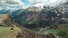 Facet z dziewczyną siedzi na skłonie góry i bierze fotografię zbiory