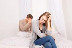 Facet z dziewczyną siedzi spęczenie na łóżku zdjęcia royalty free
