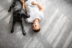 Facet z jego psim obsiadaniem bawić się w domu zdjęcie royalty free