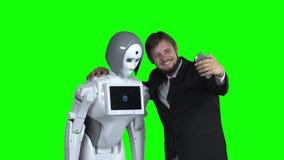 Facet z robotem fotografuje i bierze selfie zielony ekran swobodny ruch zbiory