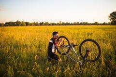 Facet załatwia rowerowego toczy wewnątrz pole przy zmierzchem Obraz Stock