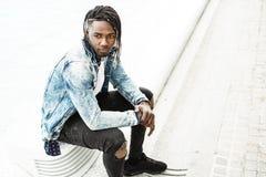 Faceta amerykanin afrykańskiego pochodzenia młody obsiadanie na ulicie Styl życia miastowi młodzi ludzie obraz royalty free